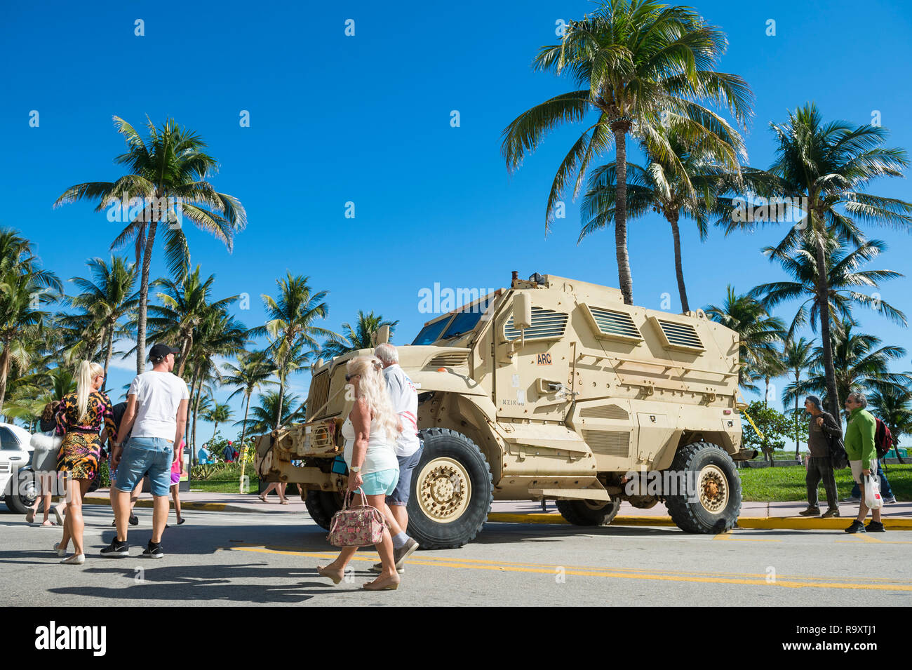 MIAMI - CIRCA DECEMBER, 2017: A military armored vehicle stands guard at Ocean Drive protecting crowds of pedestrians gathered for the holidays. - Stock Image