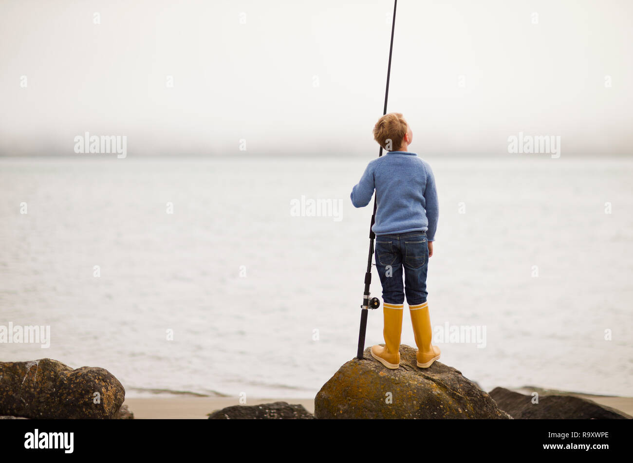 Young by standing on a rock holding a fishing rod. Stock Photo