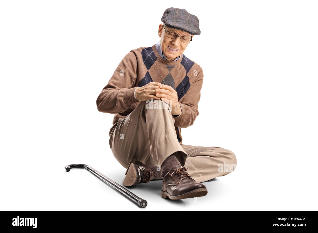 Senior man sitting on the floor and holding his painful knee - Stock Image