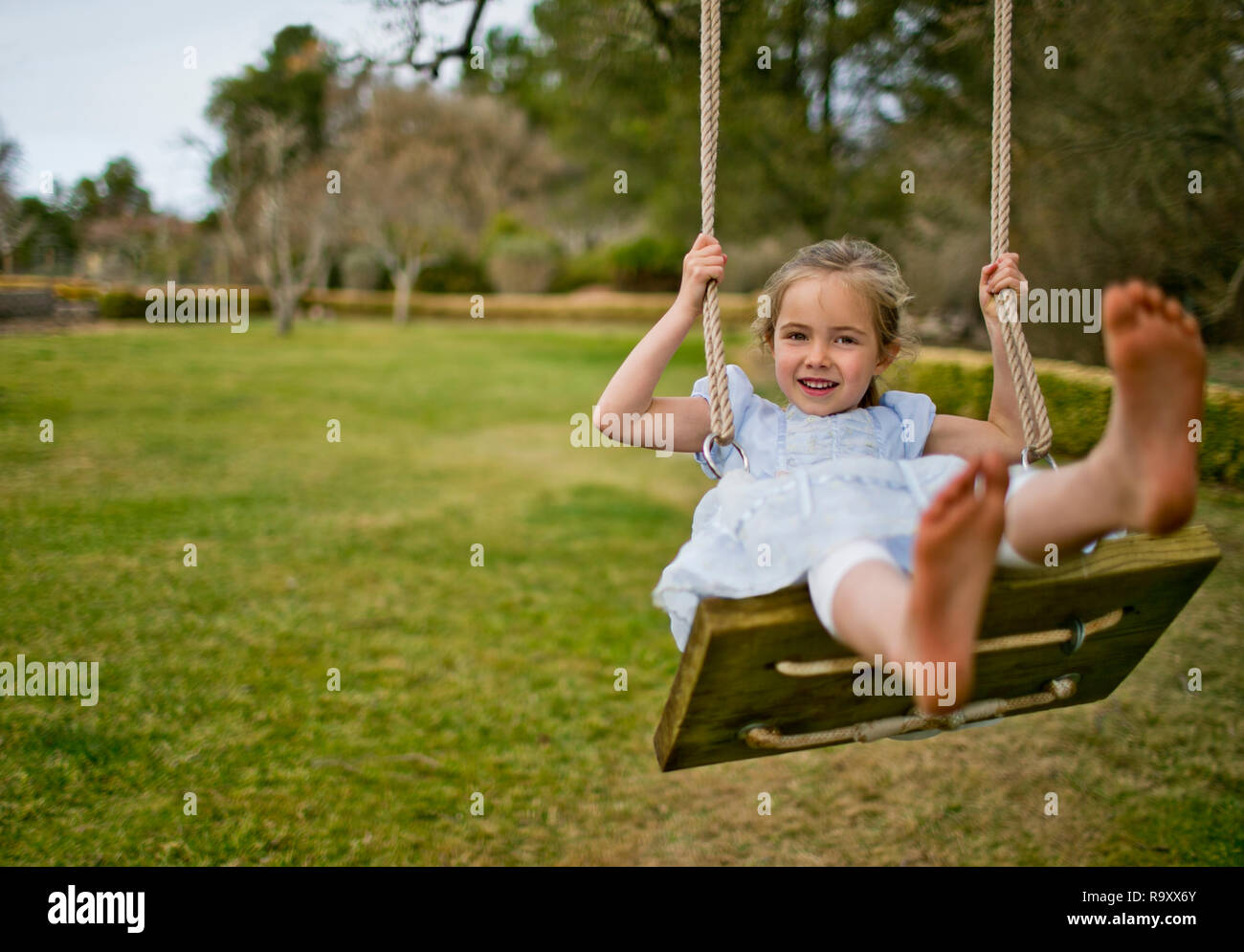 Portrait of a little girl playing on a swing in the back garden. Stock Photo
