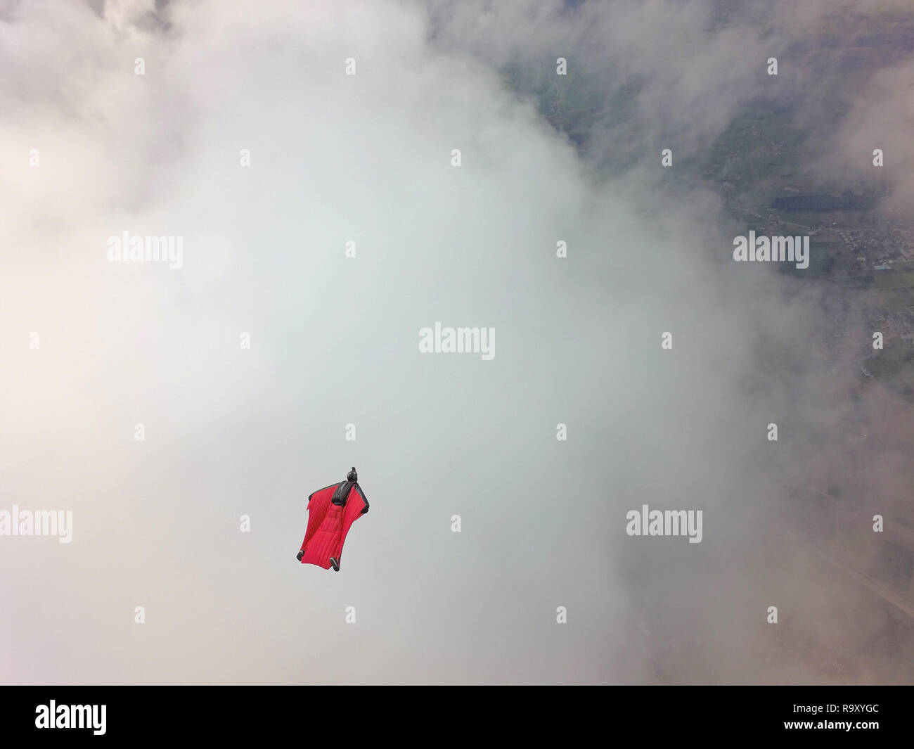 This wingsuit pilot is racing around a clound with high speed. It is fan to play within the birdman suit a soar for a long time in the sky. - Stock Image