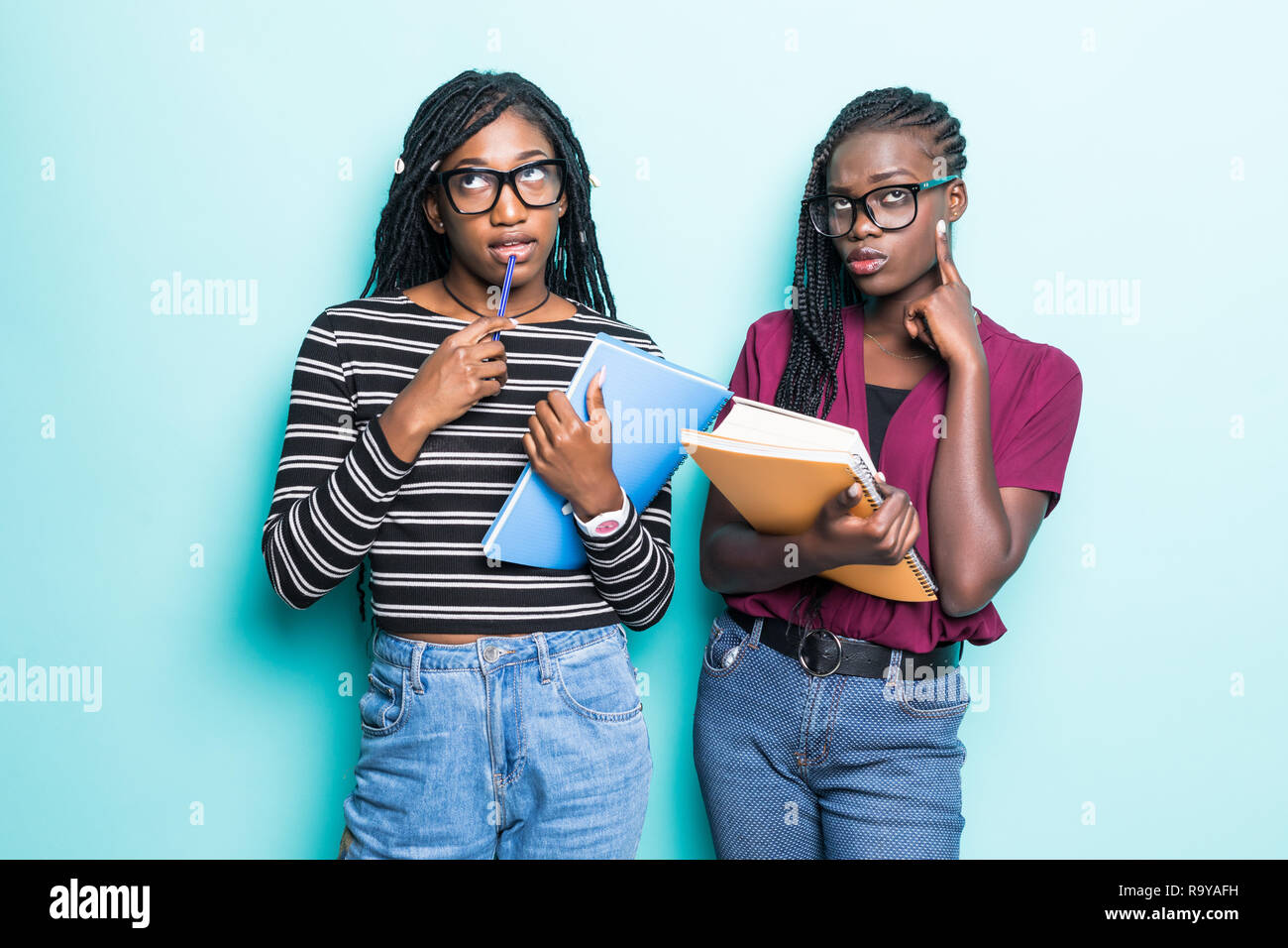 85fca3777 Portrait of two african young school teenage girls holding copybooks ...