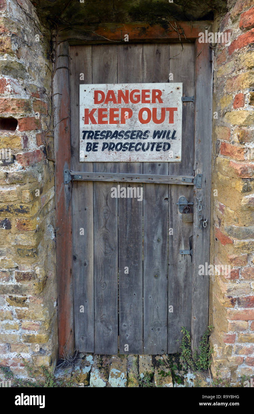 Danger, Keep Out sign on old wooden door. - Stock Image
