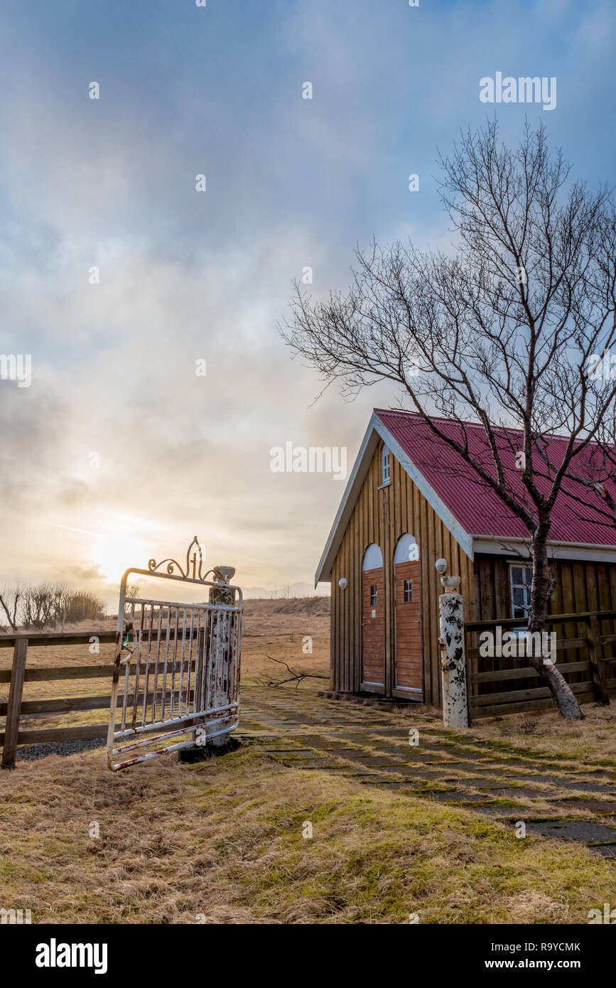 Sunset over the outhouse for the historic Kalfafellsstadur Church (established in 1927) in Iceland with a rusted gate, mountainside and tree - Stock Image