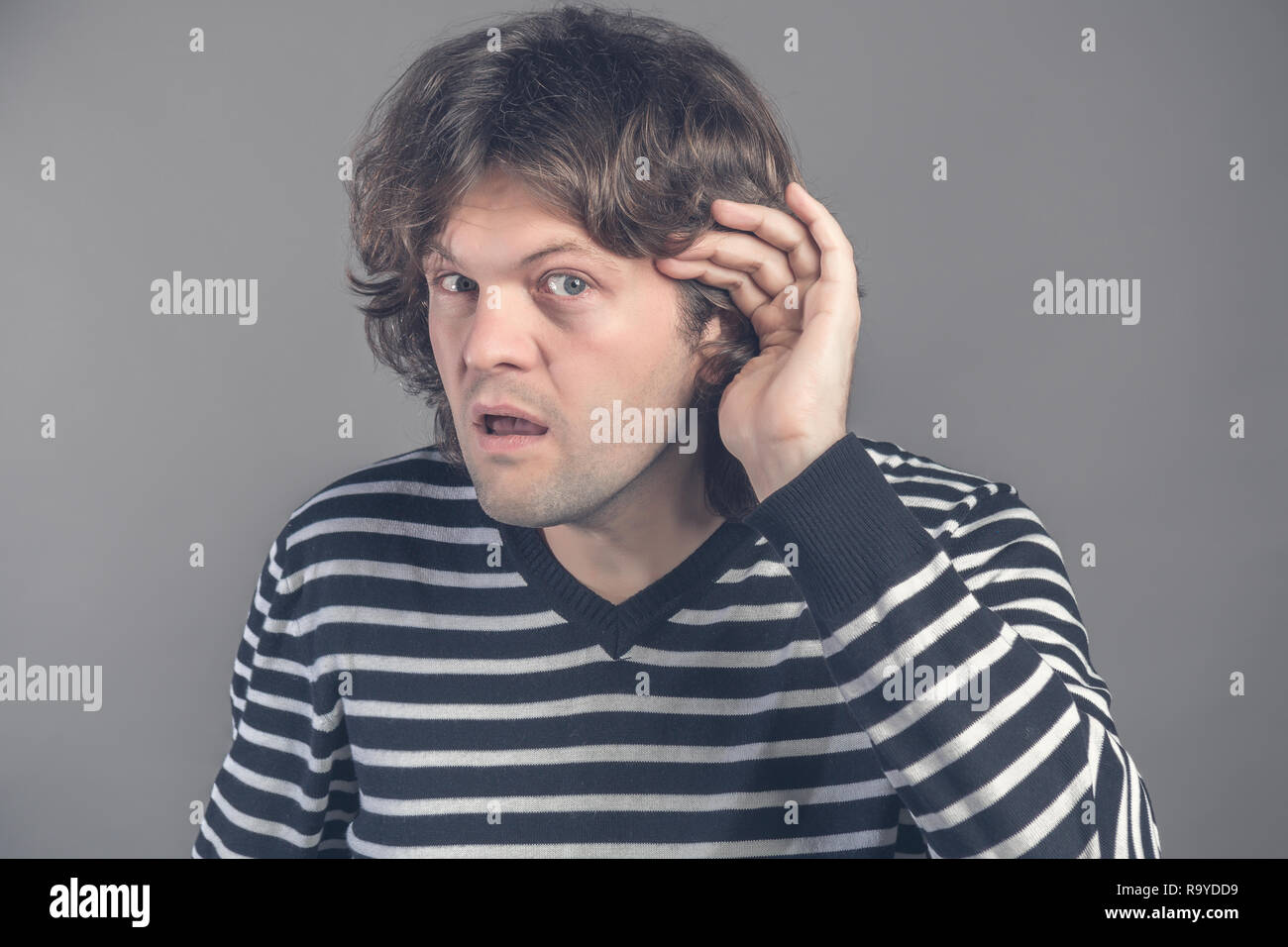 Closeup of curious or deaf man placing hand on ear asking someone to speak up or listening to bad news, isolated on grey background. Negative emotion  - Stock Image