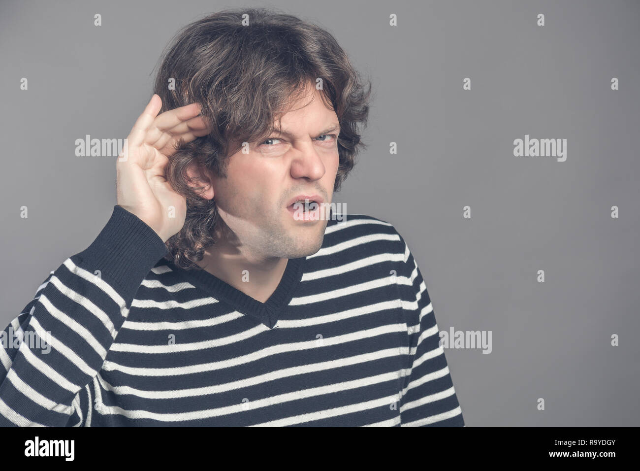 Unhappy hard of hearing man placing hand on ear asking someone to speak up or listening to bad news, isolated on gray background. Negative emotion fac - Stock Image