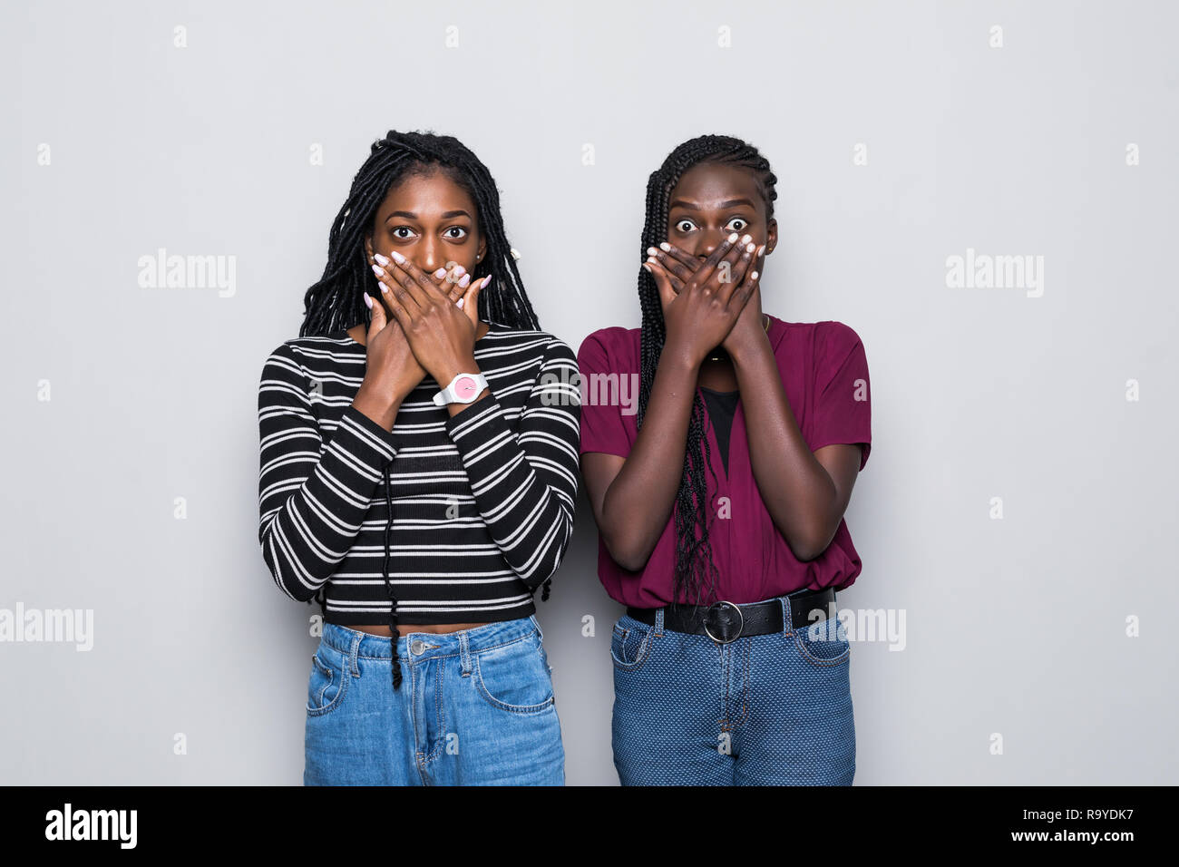 Waist up shot of shocked two african women cover mouthes with both hands, try be speechless in stressful situation isolated over gray background. - Stock Image