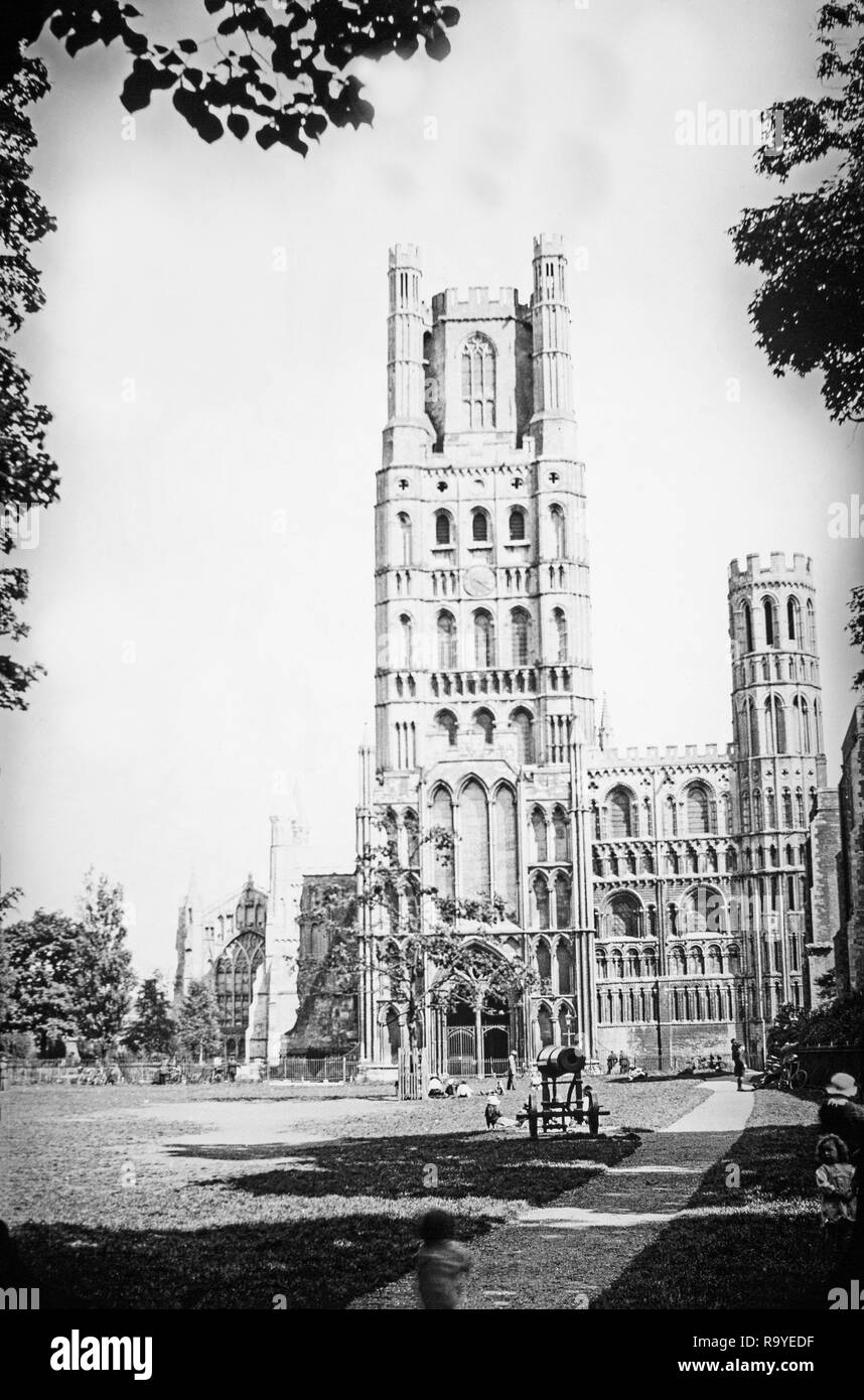 Late Victorian black and white photograph of Ely Cathedral in Cambridgeshire, England.The cathedral has its origins in AD 672 when St Etheldreda built an abbey church. The present building dates back to 1083, and cathedral status was granted it in 1109. Until the Reformation it was the Church of St Etheldreda and St Peter, at which point it was refounded as the Cathedral Church of the Holy and Undivided Trinity of Ely, continuing as the principal church of the Diocese of Ely, in Cambridgeshire. Photo also shows people relaxing in the church grounds. - Stock Image