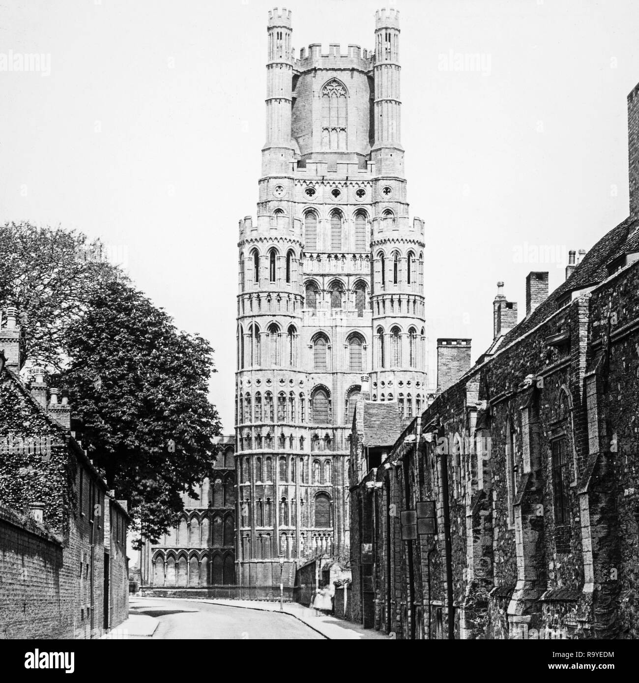 Late Victorian black and white photograph of Ely Cathedral in Cambridgeshire, England.The cathedral has its origins in AD 672 when St Etheldreda built an abbey church. The present building dates back to 1083, and cathedral status was granted it in 1109. Until the Reformation it was the Church of St Etheldreda and St Peter, at which point it was refounded as the Cathedral Church of the Holy and Undivided Trinity of Ely, continuing as the principal church of the Diocese of Ely, in Cambridgeshire. Photo also shows houses in the village. - Stock Image