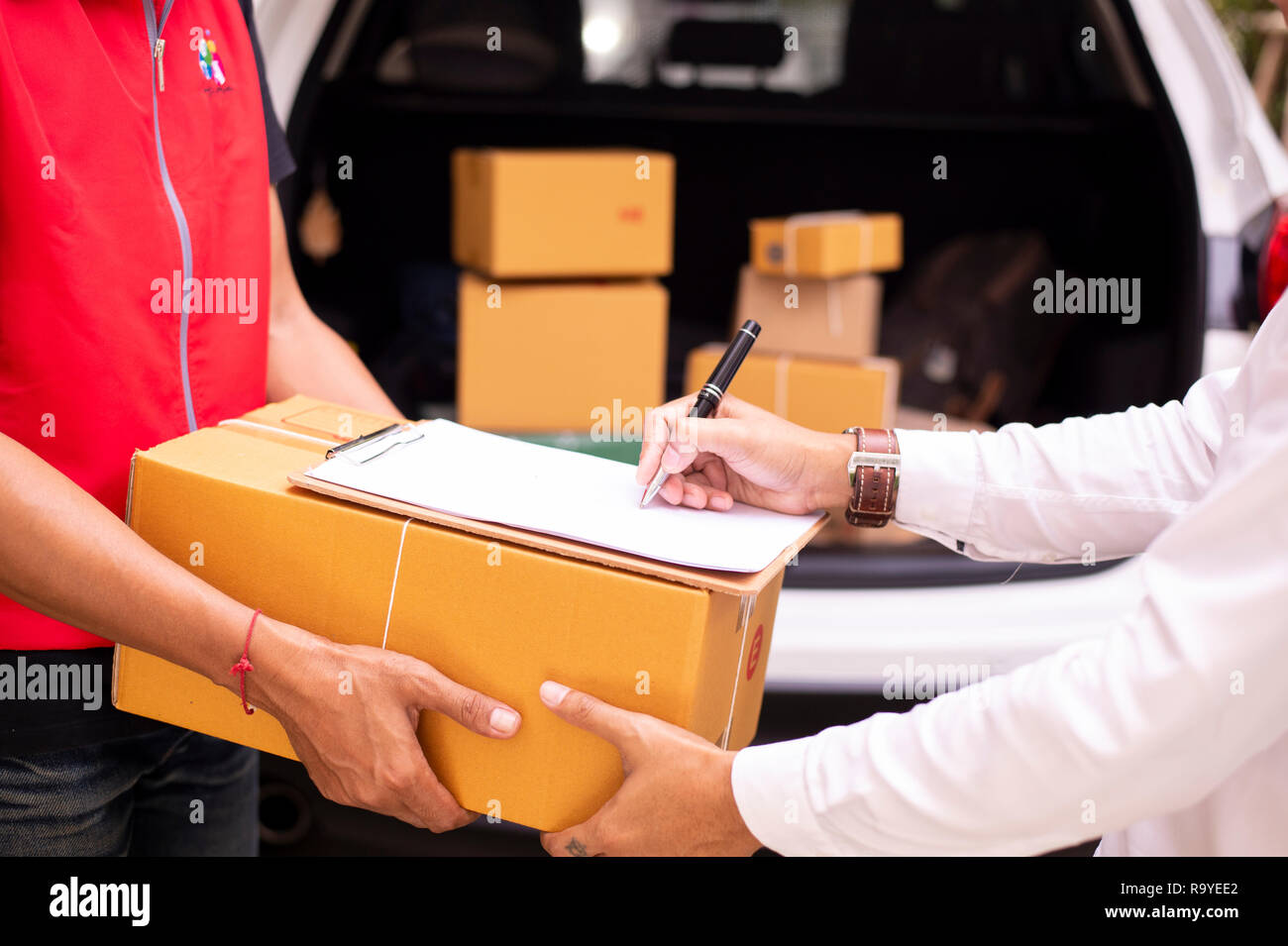 Asian young man and delivery worker are signing documents for send parcels, cardboard boxes in the background - Image - Stock Image