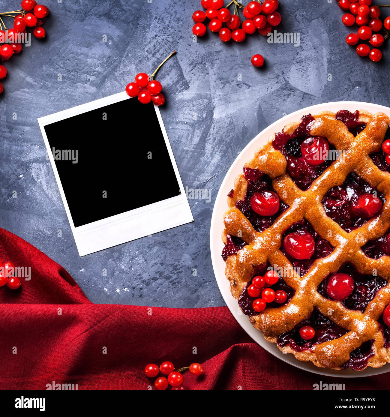Blank photo frame near homemade cherry pie on grunge background - Stock Image