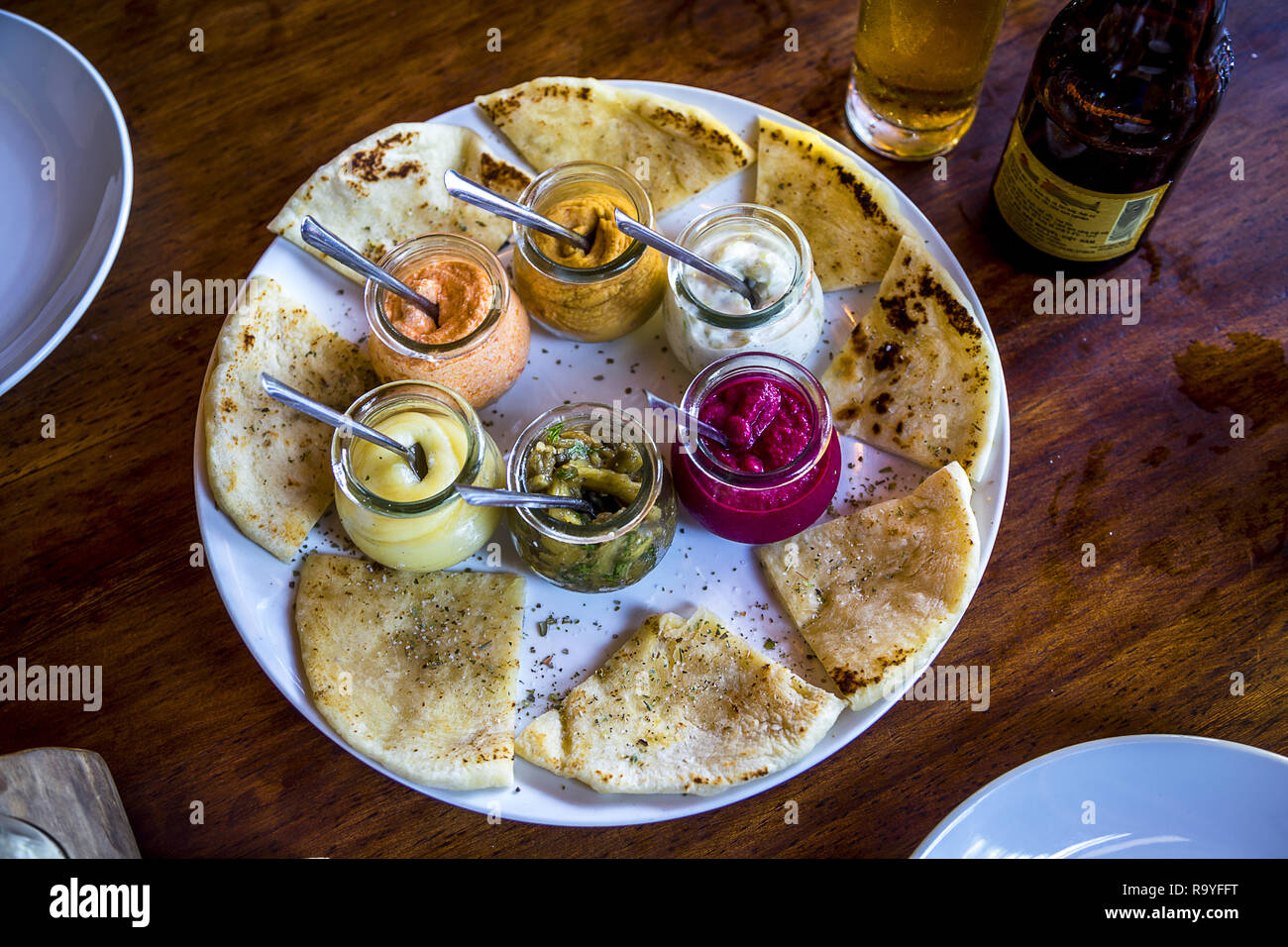 plate of flat bread and assorted humus in jars. - Stock Image