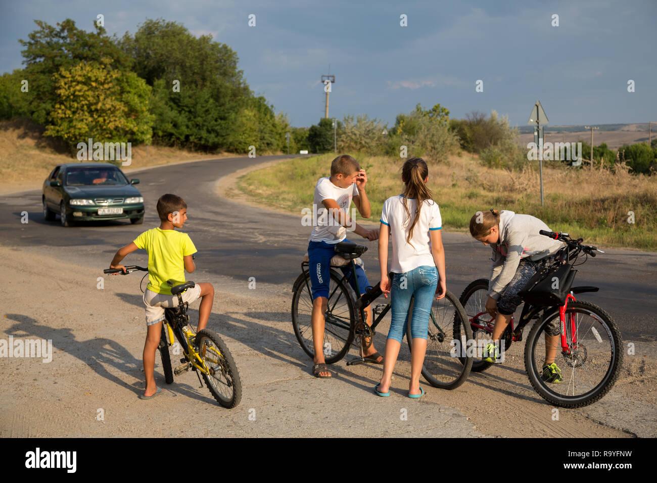 30.08.2016, Causeni, Rajon Causeni, Republik Moldau - Kinder mit Fahrraedern an einer Landtrasse schlagen die Zeit tot. 00A160830D441CARO.JPG [MODEL R Stock Photo