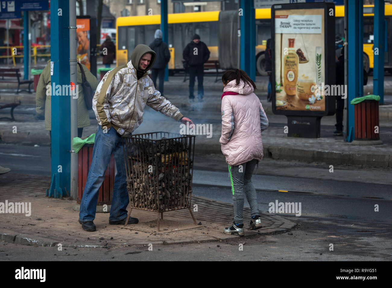28.02.2018, Bytom (Beuthen), Schlesien, Polen - Menschen an einer Bushaltestelle waermen sich an einem Gefaess mit brennender Steinkohle. 00A180228D14 Stock Photo