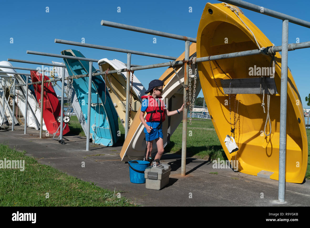 Small boy in red life-jacket with blue bucket and fishing gear waits patiently by dinghy to go fishing at Tauranga marina, New Zealand. - Stock Image