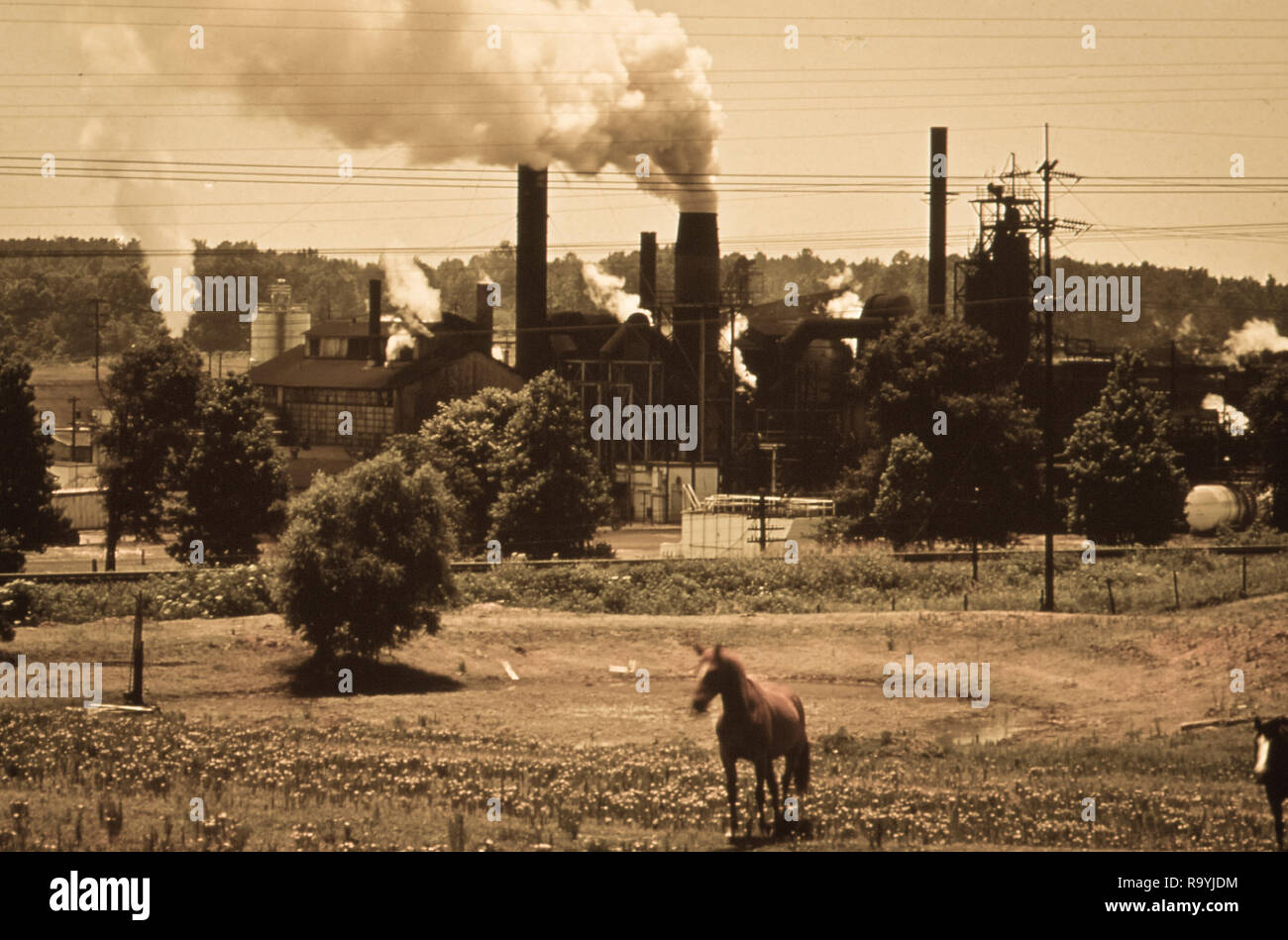 Smoke billows from industrial smokestacks in America affecting life Stock Photo