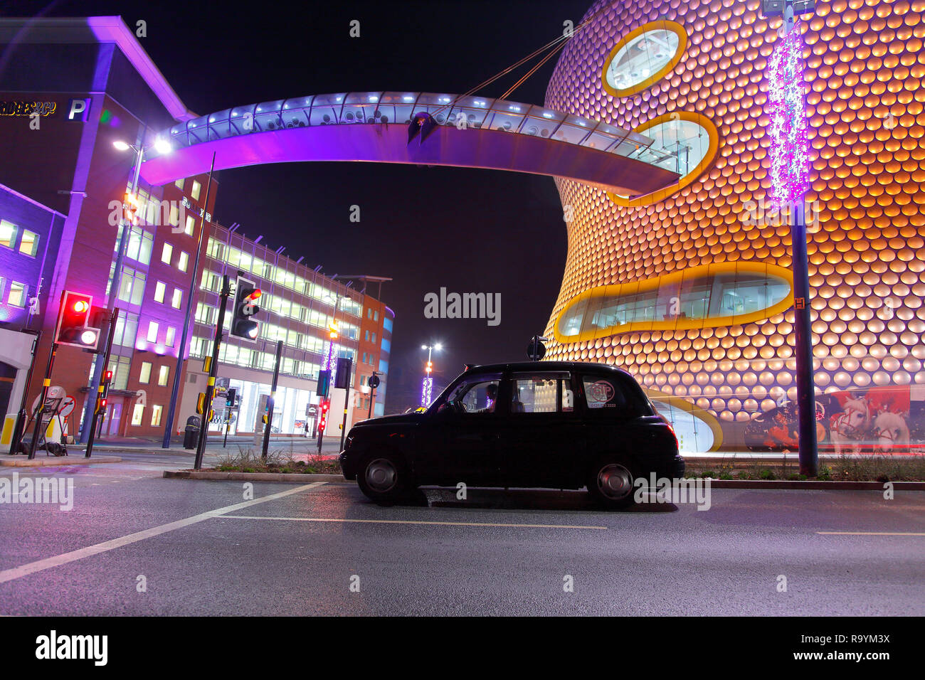 A Black Hackney Carriage waiting at traffic lights outside Selfridges in Birmingham City Centre. - Stock Image