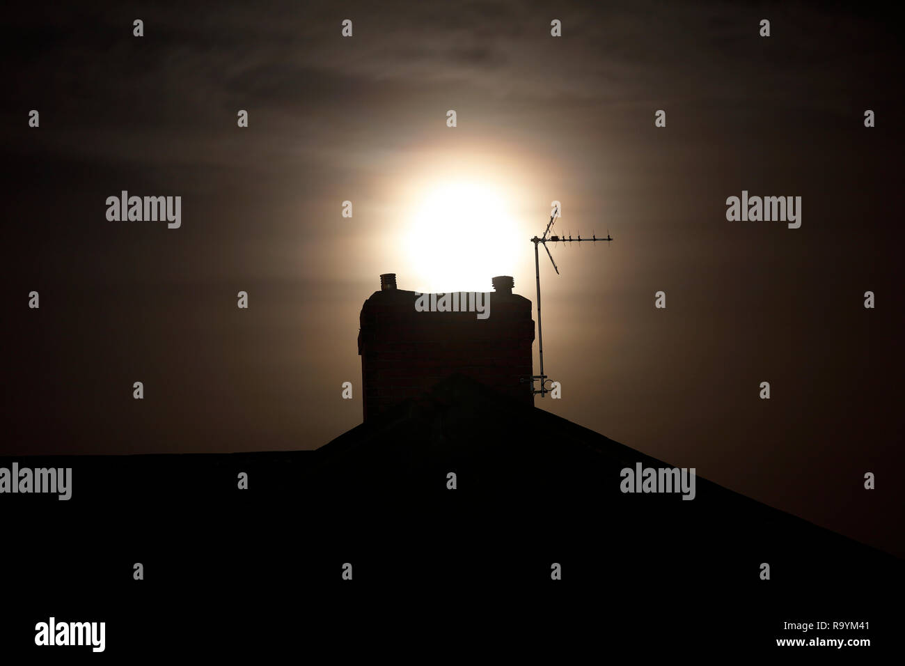 The moon behind a rooftop chimney - Stock Image