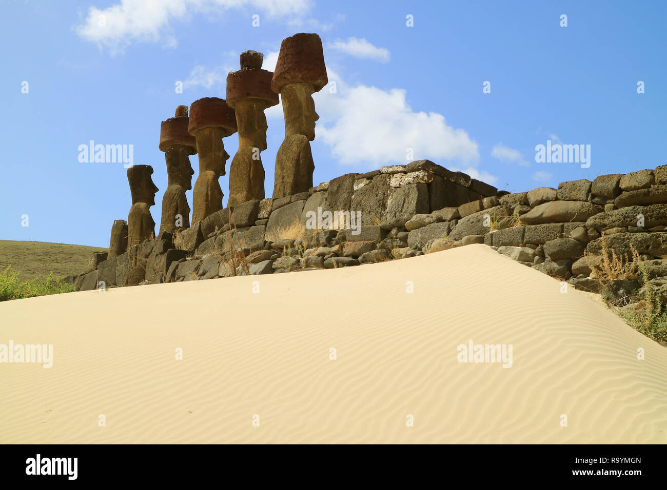 Seven gigantic Moai statues of Ahu Nau Nau ceremonial platform surrounded by soft coral sand of Anakena beach, Easter island, Chile - Stock Image