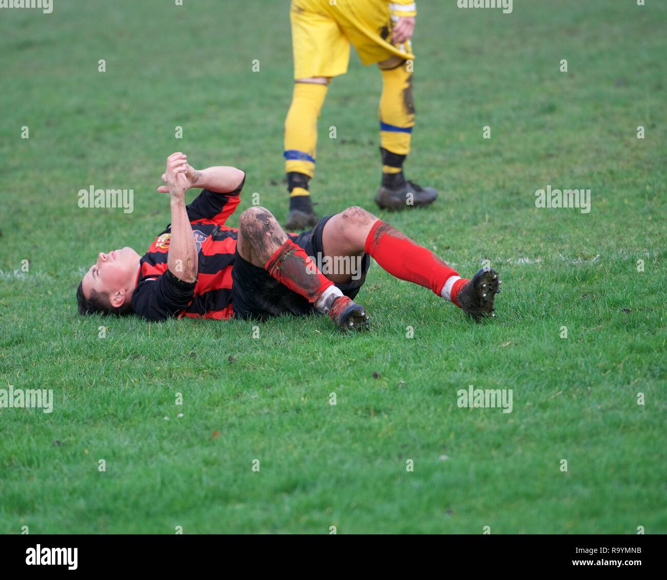 Sports injury in the match between Buxwotth( red and black0 and Melandra Castle (yellow) in the Hope Valley Amateur League on December 29th, 2018. Stock Photo