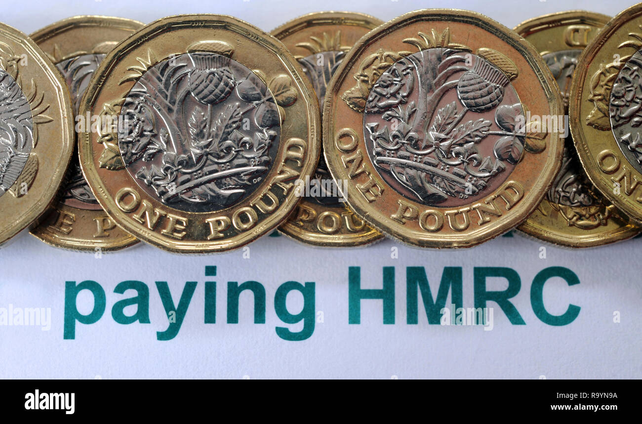 BRITISH ONE POUND COINS WITH HMRC LITERATURE RE PAYING PAYMENTS HER MAJESTYS REVENUE AND CUSTOMS TAX ETC - Stock Image