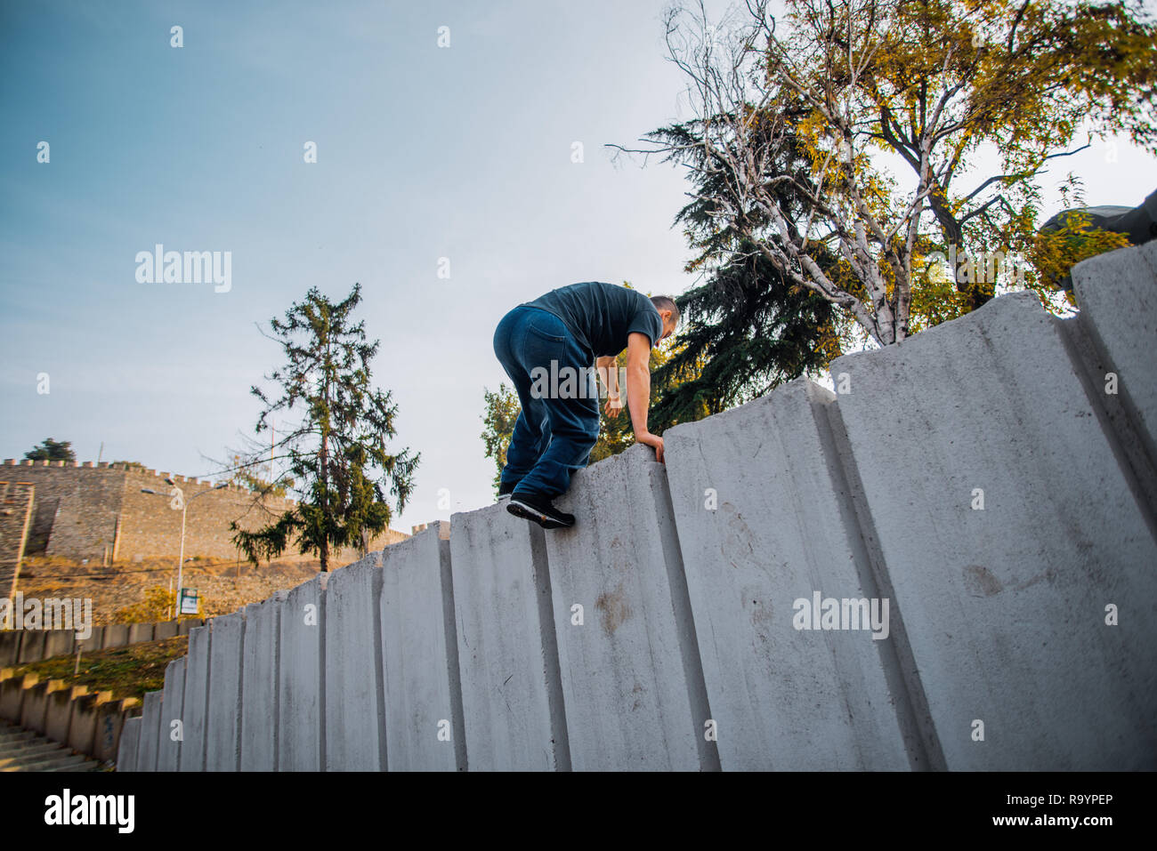 Traceur man hiking on the concrete obstacle while exercising parkour - Stock Image