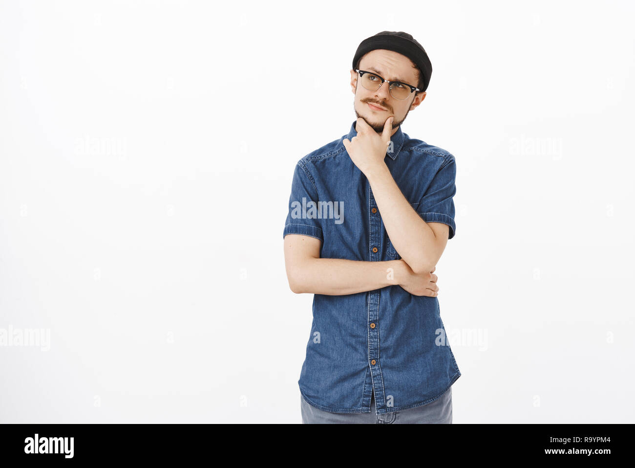 Indoor shot of thoughtful attractive adult caucasian guy in black beanie and glasses rubbing moustache on chin looking at upper left corner concentrated thinking, making decision or choice in mind - Stock Image