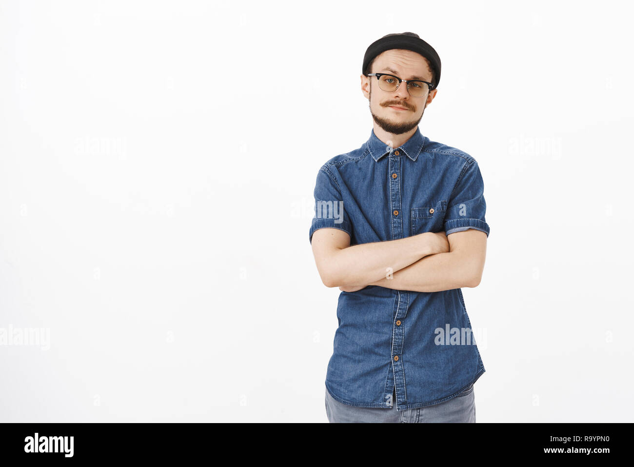 Unimpressed try better. Displeased uninterested snobbish and arrogant guy with moustache in glasses and black beanie holding hands crossed on chest raising eyebrow from disbelief and doubt - Stock Image