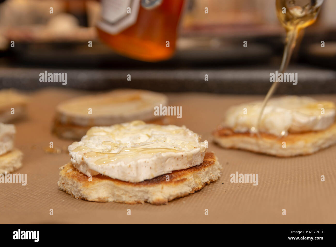 Pouring of honey over roasted bred with a slice of chevre cheese. - Stock Image