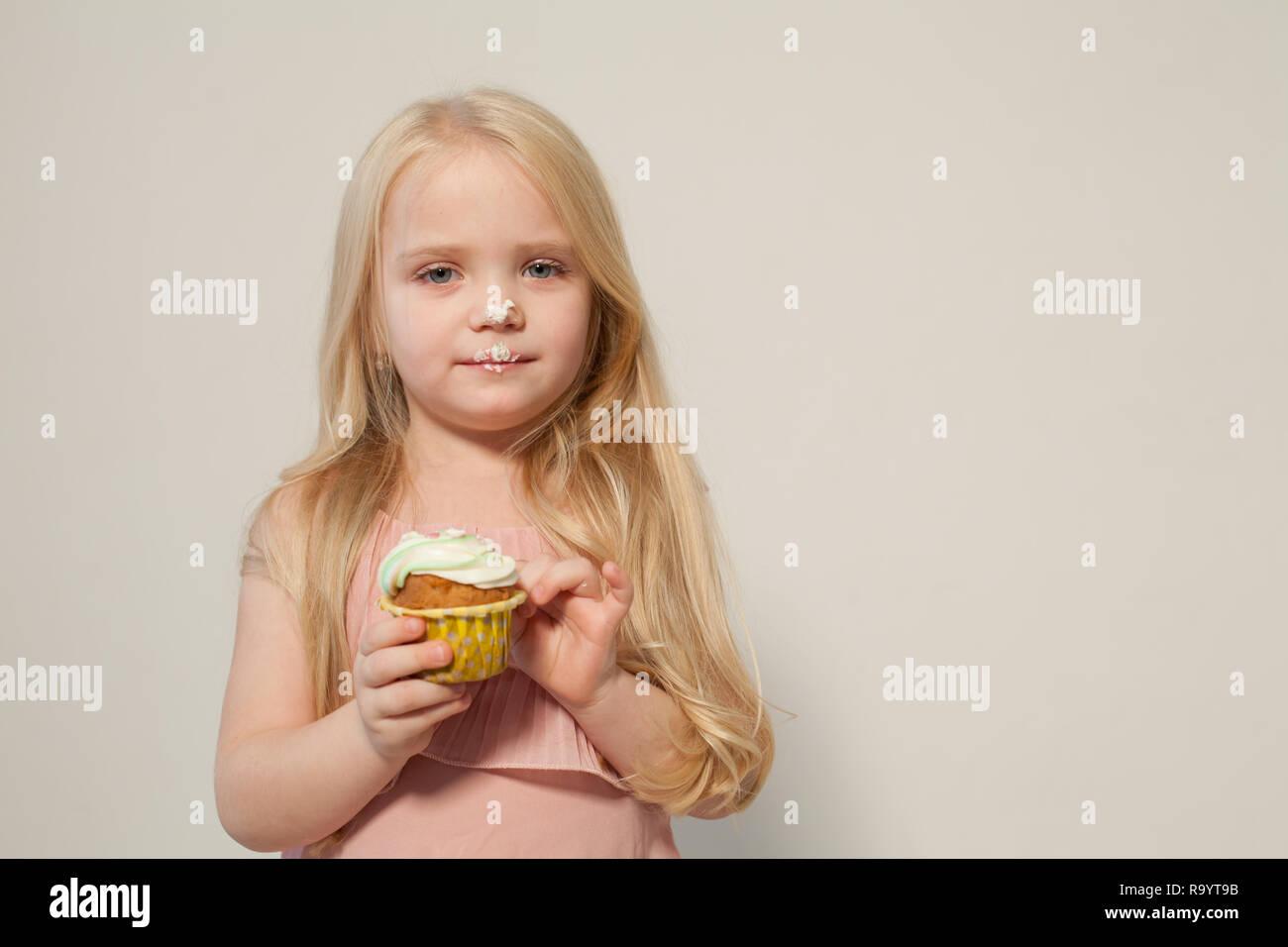 little girl eating cake with cream cupcake sweet - Stock Image