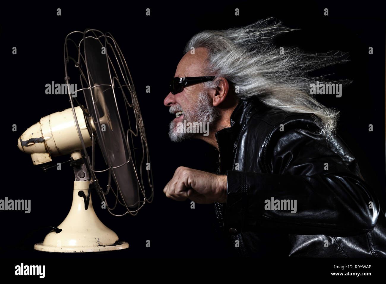 Bikers dream, long haired man simulating a motorbike ride in front of a fan - Stock Image