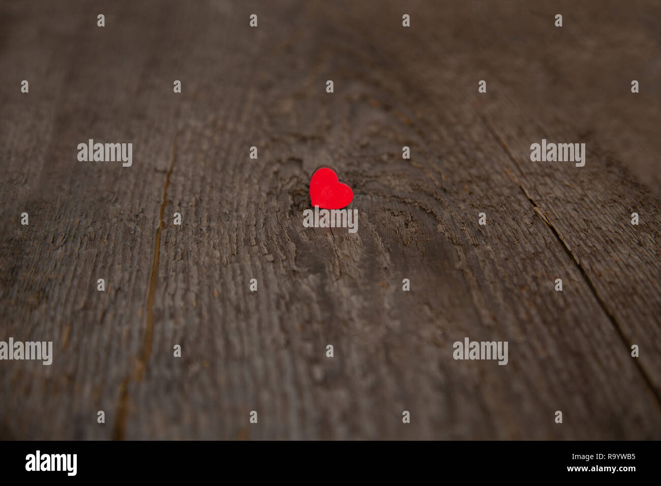 Small wooden red heart on an old dry wooden board for Valentine's Day close up - Stock Image