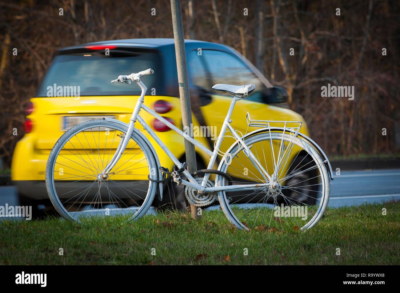 Cars pass a Ghost Bike on a section of road in Halle (Saale), Germany. - Stock Image