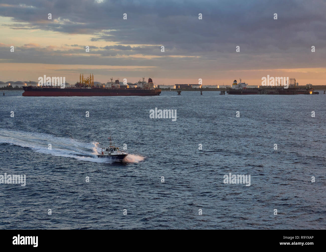 The Pilot Boat passing the Offshore Jetties and coming out to a Vessel at the Anchorage in Freeport, Grand Bahama in the Caribbean - Stock Image