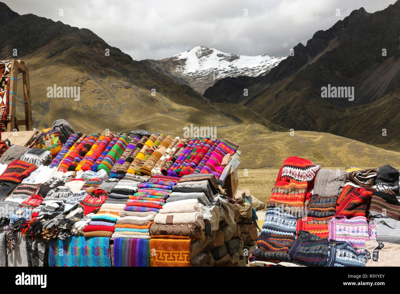 Scarves, hats in traditional style of different colors on the market. The road Cusco-Puno, Peru - Stock Image