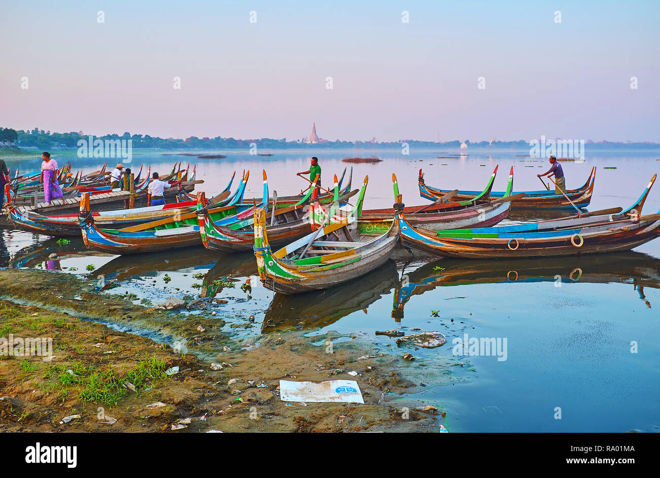 AMARAPURA, MYANMAR - FEBRUARY 21, 2018: The colorful wooden canoes weit the tourists in port on Taungthaman Lake and offers sunset trip to U Bein Brid - Stock Image