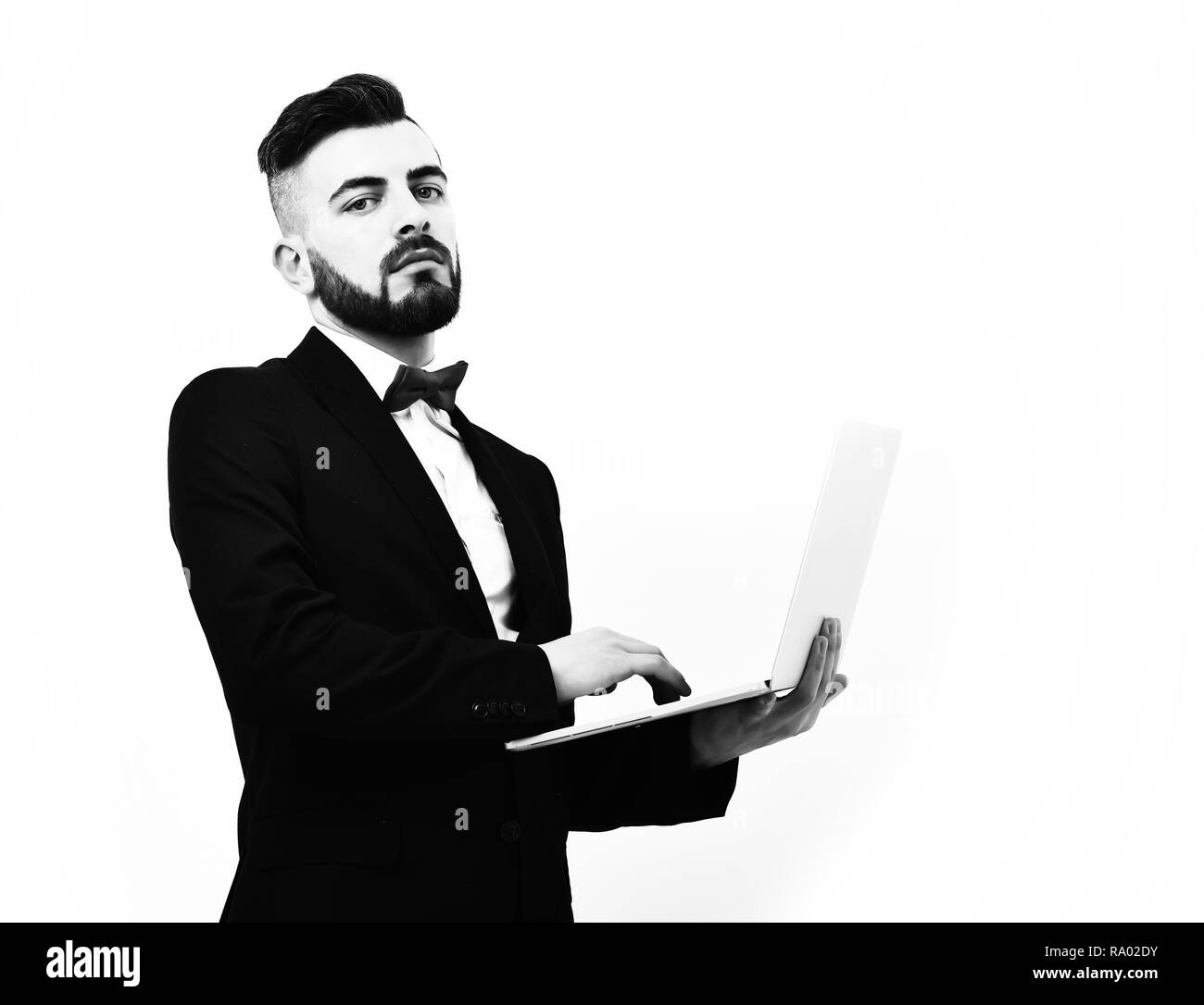 Businessman or insurance agent with beard and moustache, attentive look and serious face works on his laptop, isolated on white background, copy space. Concept of high technology and working online - Stock Image