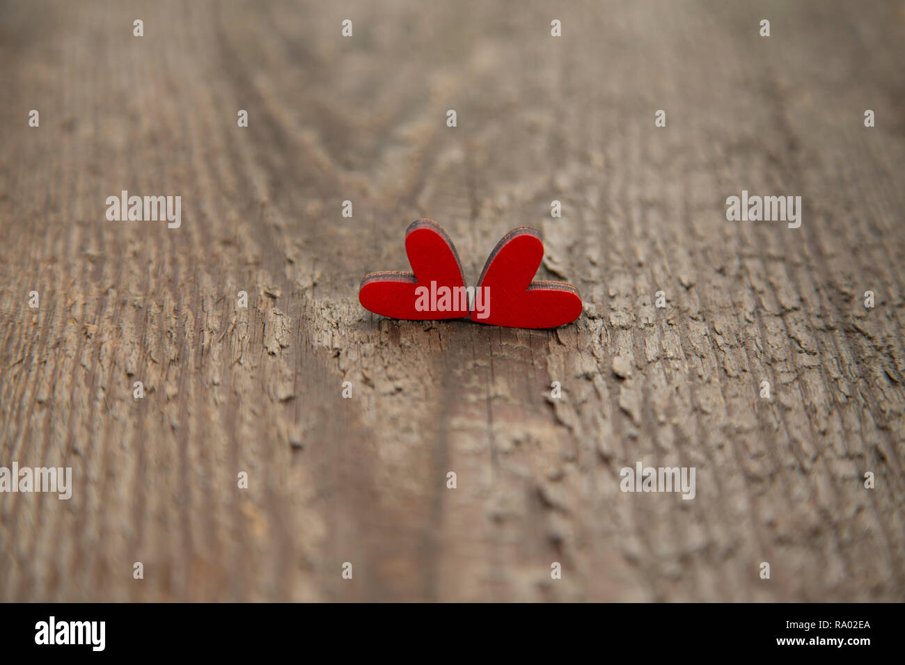 Two wooden red hearts on an old dry wooden board for Valentine's Day close-up. - Stock Image