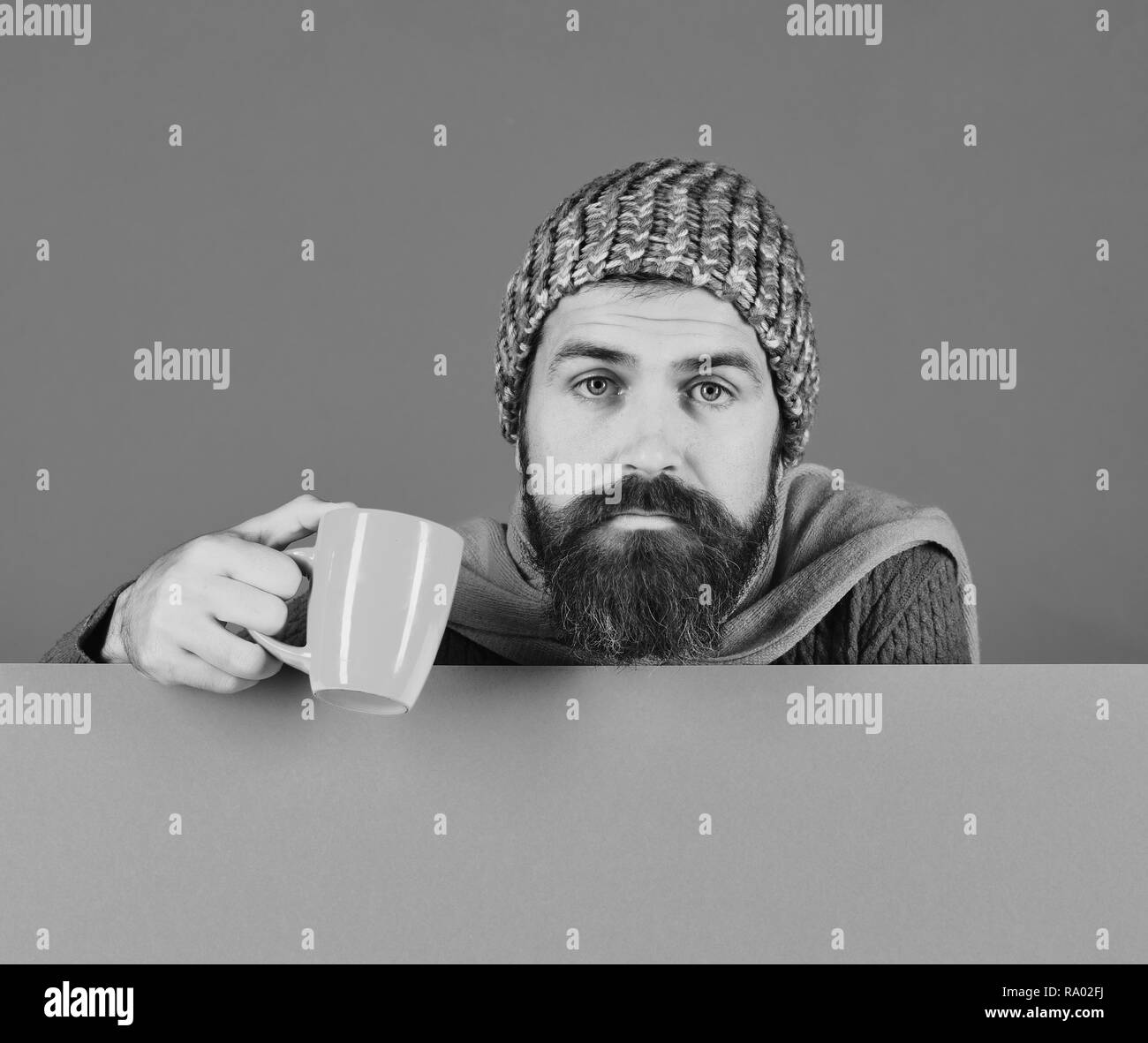 Fall season and influenza. Man with beard holds orange cup of medicine. Illness and autumn sickness concept. Guy with tired or depressed face wears warm hat on green and cyan background, copy space - Stock Image