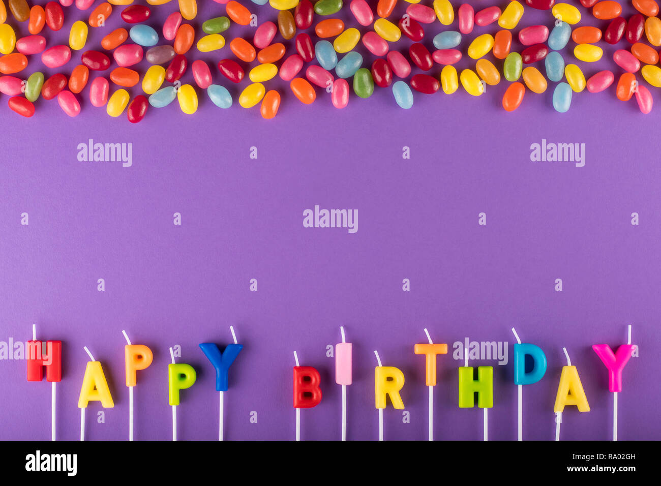 Colorful Happy Birthday candles for cake and jelly beans - Stock Image