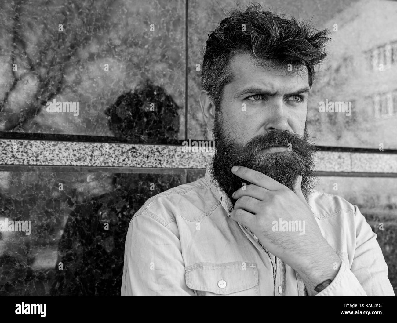Masculinity concept. Hipster with tousled hair touches beard while looking into distance. Guy looks suspicious. Man with beard and mustache on thoughtful, pensive face, black marble background. - Stock Image