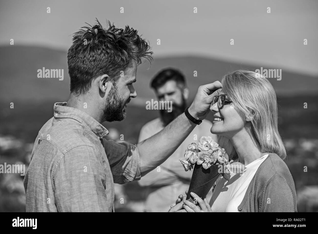Couple in love dating while jealous husband fixedly watching on background. Unrequited love concept. Lovers meeting outdoor flirt romance relations. Couple romantic date lover present bouquet flowers. - Stock Image