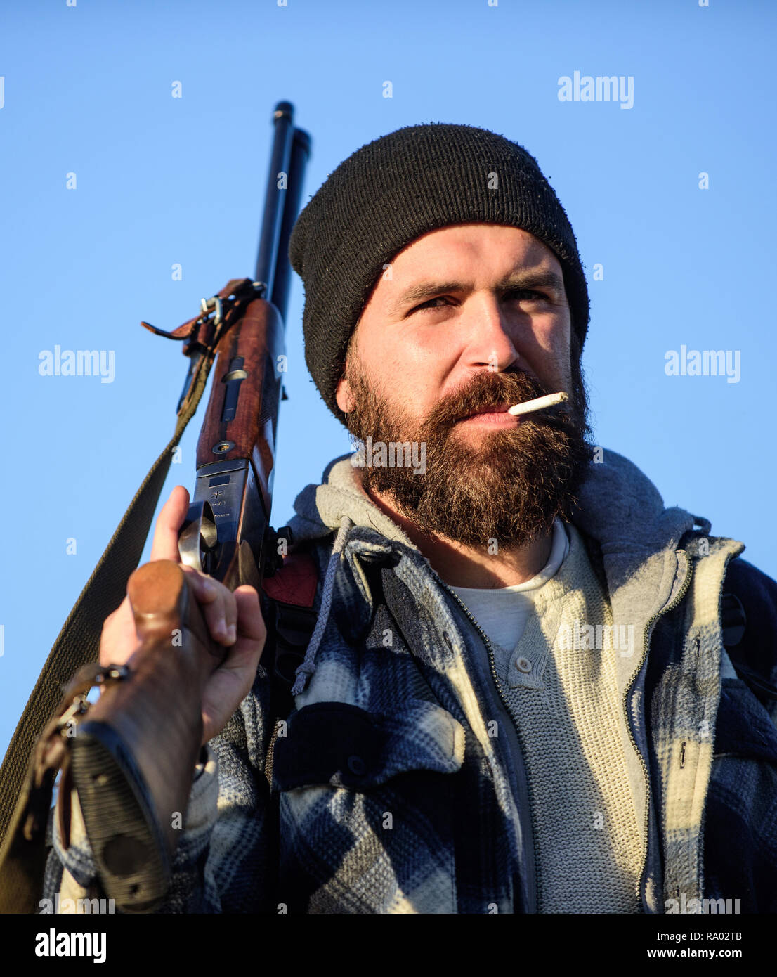 Hunter with rifle gun close up. Guy bearded hunter spend leisure hunting and smoking. Hunting masculine hobby concept. Man brutal bearded guy gamekeeper blue sky background. Brutality and masculinity. - Stock Image