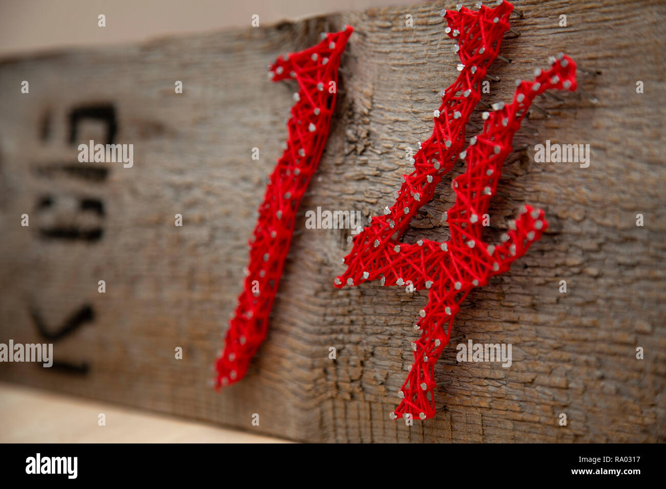 number 14 in red threads on an old dry board - Stock Image
