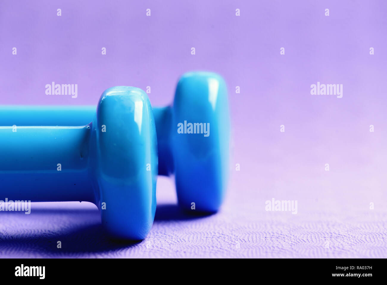 Sports and healthy lifestyle concept. Barbells made of plastic, close up. Shaping and fitness equipment. Dumbbells in cyan blue color on purple background, selective focus - Stock Image