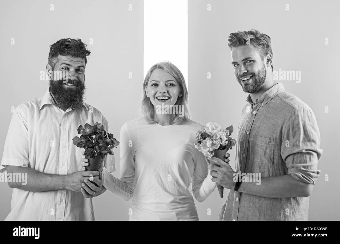 Girl popular receive lot men attention. Girl happy likes gifts. Love triangle. Men competitors with bouquets flowers try conquer girl. Woman smiling can not choose partner, grabs both bouquets. - Stock Image
