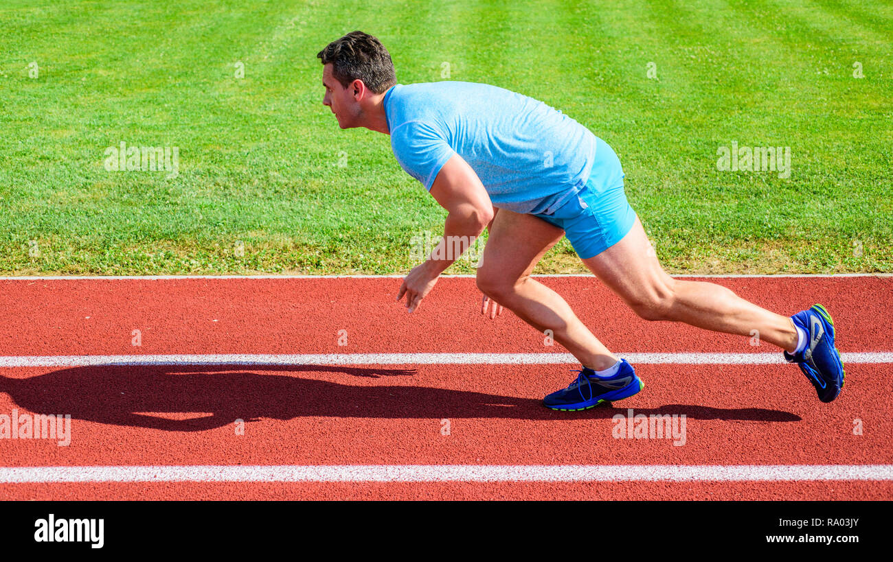 Man athlete runner push off starting position stadium path sunny day. Runner captured in motion just after start of race. Runner sprint race at stadium. How to start running. Boost speed concept. - Stock Image