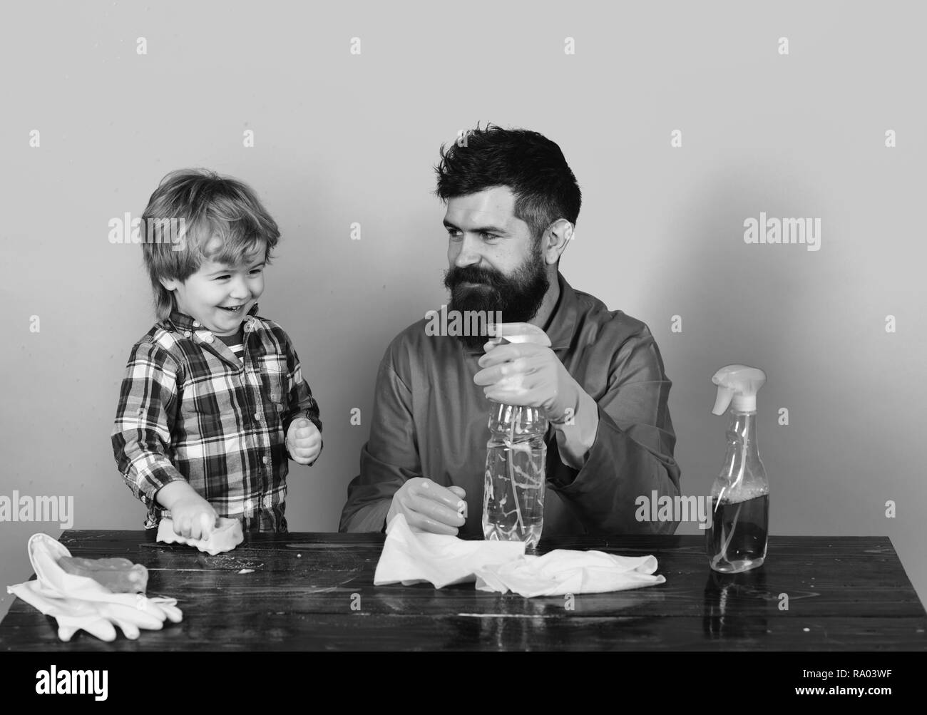 Guy with beard and mustache with rubber gloves holds spray. Man with smiling child at wooden table on blue background. Father and son plays with cleaning props. Cleaning activities concept. - Stock Image