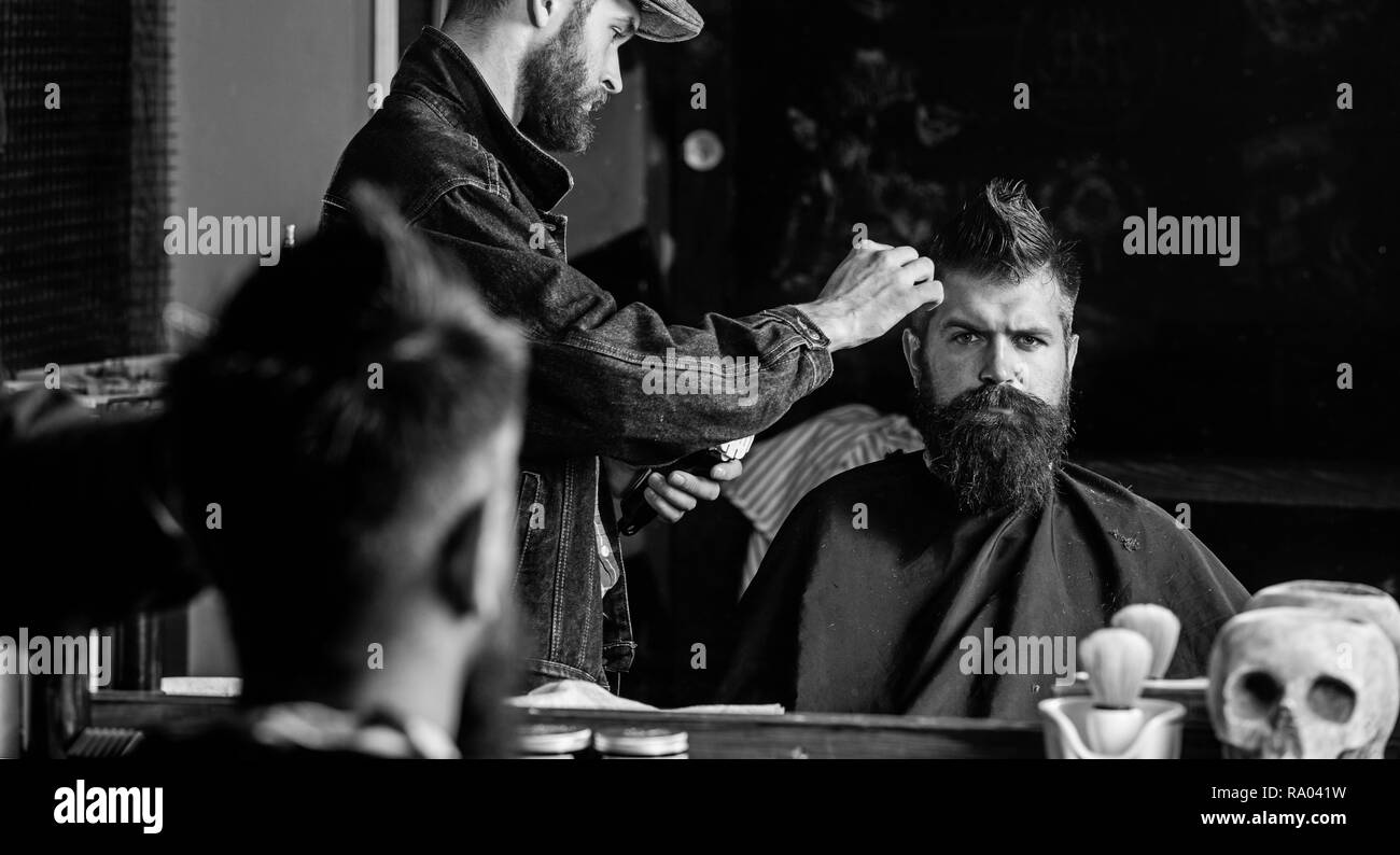 Hipster client getting haircut. Barber with hair clipper works on hairstyle for man with beard, barbershop background. Haircut concept. Barber styling hair of brutal bearded client with clipper. - Stock Image