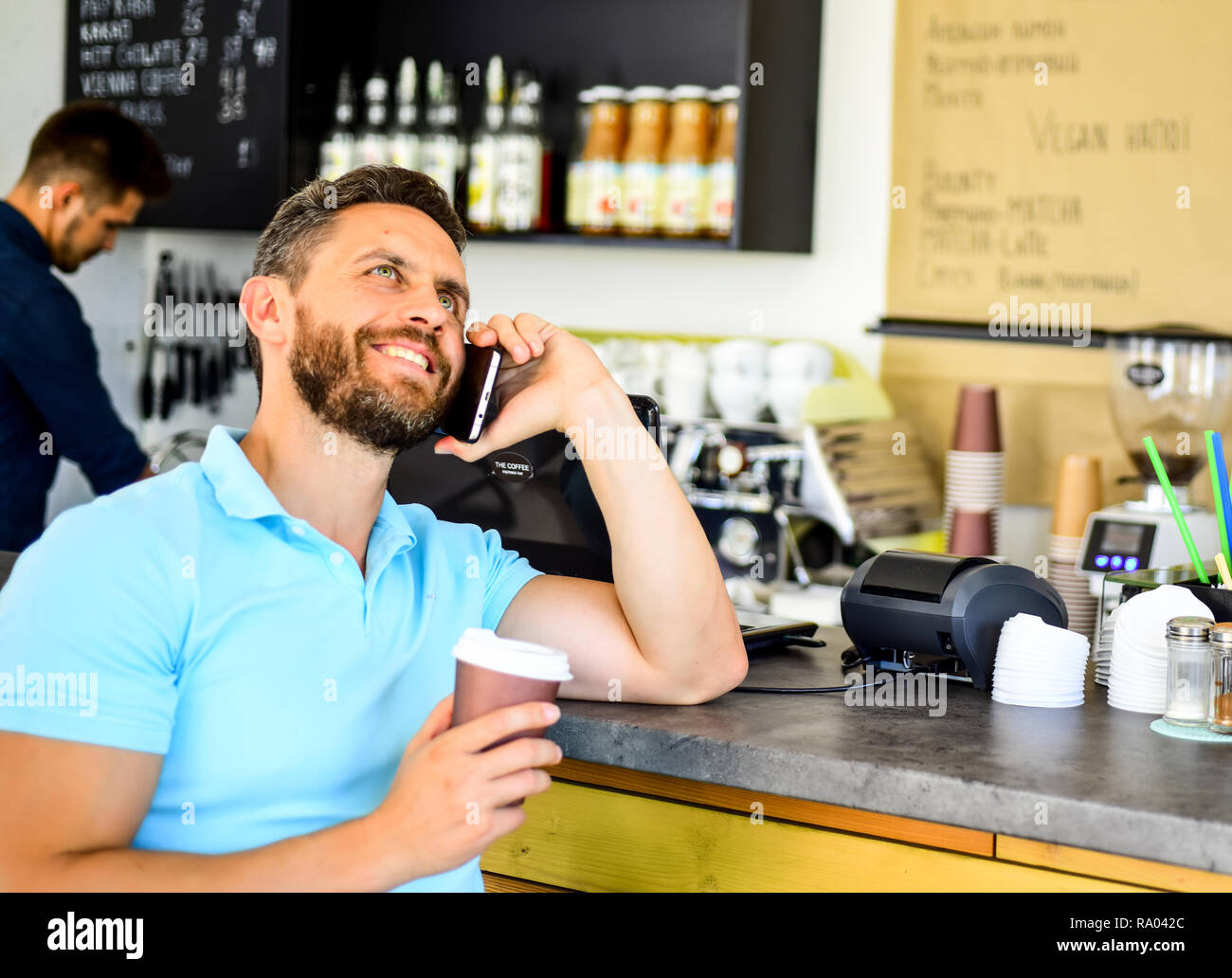 Coffee take away option for busy people. Man mobile conversation cafe barista background. Drink coffee while waiting. Waiting for you. Man smartphone order coffee in cafe. Coffee break concept. - Stock Image